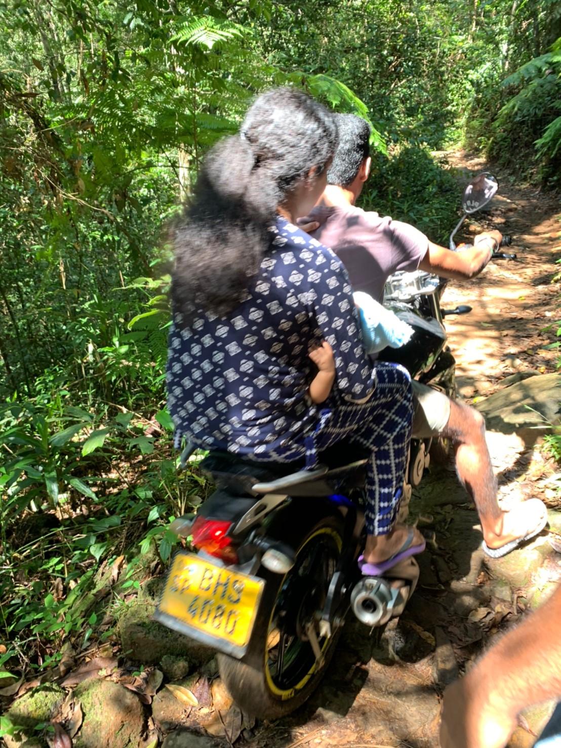 バイクでシンハラージャ森林保護区を往来する人々
